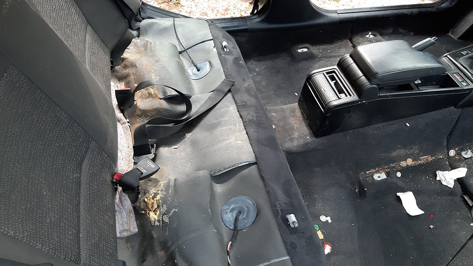 car back seat removed with all the trash under