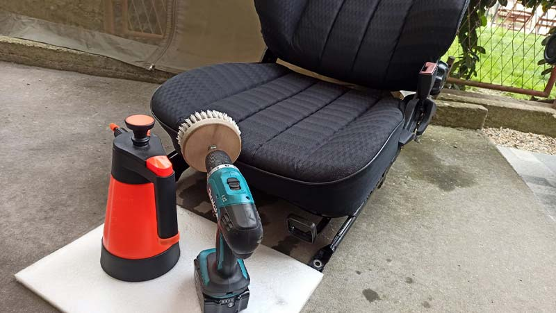 using carpet cleaning solution and drill brush to clean car seats